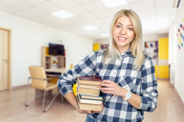 Beautiful young woman holding books