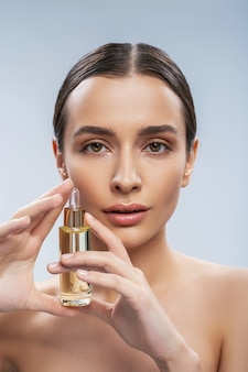 Beautiful young woman holding bottle of facial serum