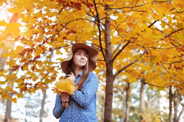 Beautiful young woman holding a bunch of autumn leaves