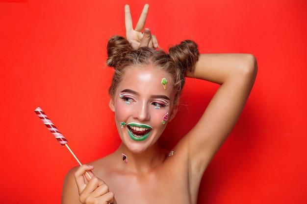 Красивая молодая женщина, держащая конфету, широко улыбаясь