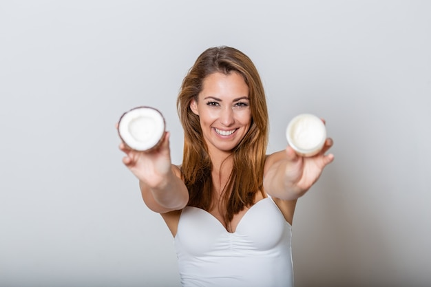 Beautiful young woman holding coconut slice and white natural beauty cream