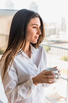 Beautiful young woman holding coffee cup in hand