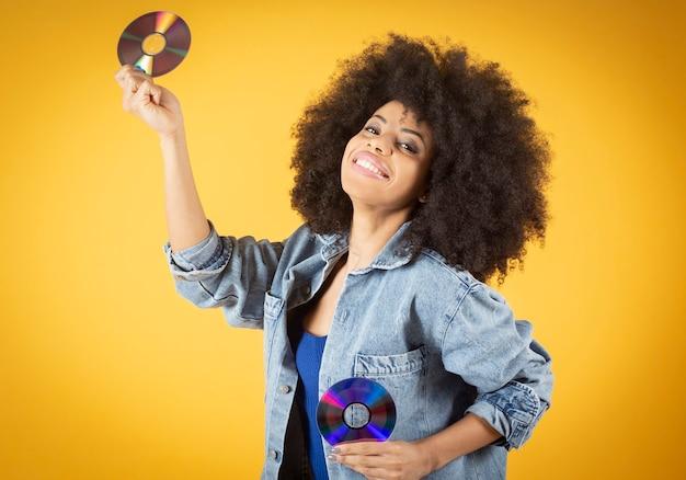 コンパクトディスクを保持し、カメラに微笑んで美しい若い女性。
