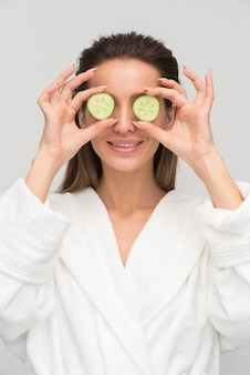 Beautiful young woman holding cucumber slices against her eyes