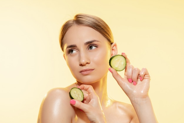 Beautiful young woman holding cucumber slices