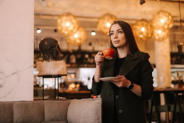 레스토랑에 서 있는 동안 맛있는 뜨거운 커피 한 잔을 손에 들고 있는 아름다운 젊은 여성
