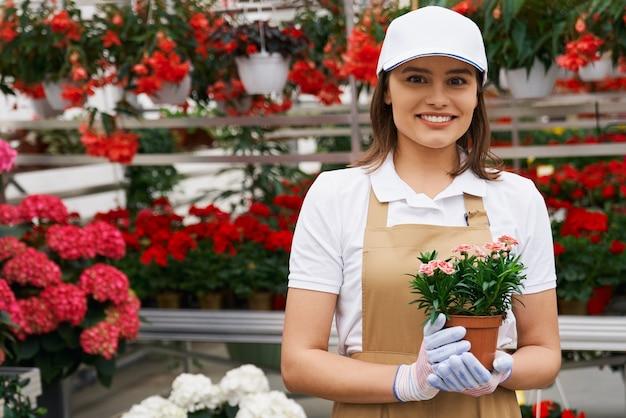 Bella giovane donna che tiene carino vaso di fiori in serra