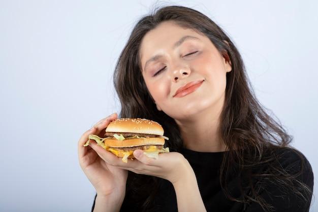 Красивая молодая женщина держит вкусный бургер из говядины и мечтает.