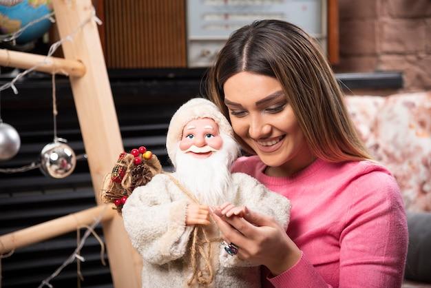 家で人形を保持している美しい若い女性。