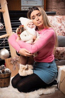 Bella bambola della tenuta della giovane donna a casa.