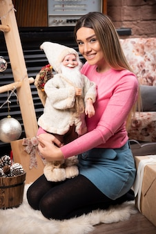 Beautiful young woman holding doll and smiling.