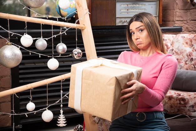 집에서 선물 상자를 들고 있는 아름다운 젊은 여성