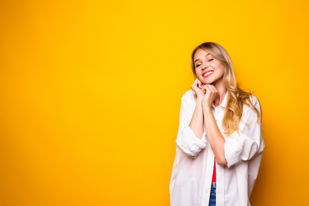 Beautiful young woman holding hand on chin, smiling,  on yellow wall.