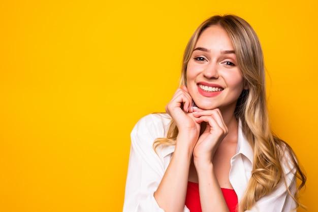 Красивая молодая женщина, держащая руку на подбородке, улыбаясь, на желтой стене.