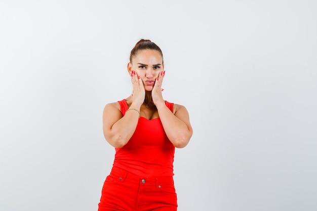 Bella giovane donna che tiene le mani sulle guance in canottiera rossa, pantaloni e guardando meravigliato. vista frontale.