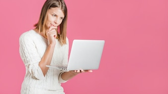 Beautiful young woman holding laptop on pink backdrop