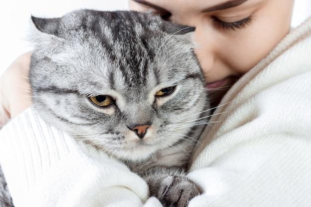 손에 작은 새끼 고양이를 들고 그에게 결합하는 아름 다운 젊은 여자