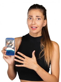 Beautiful young woman holding out her broken touch screen mobile phone