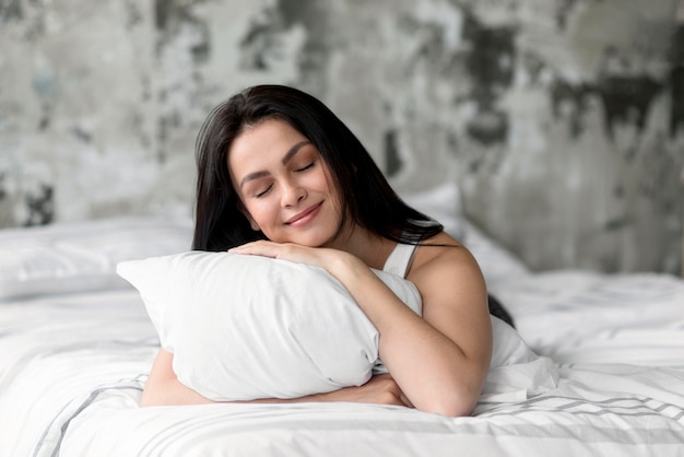 Beautiful young woman holding pillow