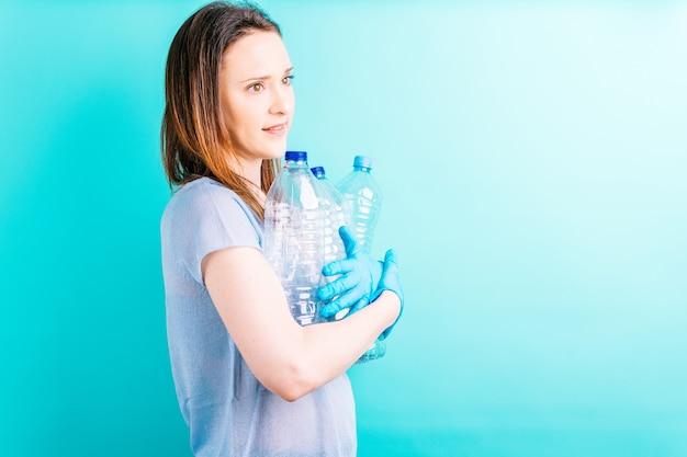 青い背景にペットボトルを保持している美しい若い女性。リサイクルの概念。環境への配慮