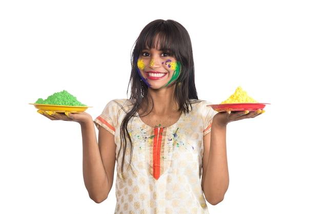 Красивая молодая женщина, держащая порошковый цвет в тарелке по случаю фестиваля холи.
