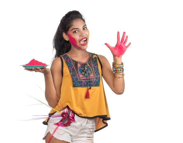 Красивая молодая женщина, держащая напудренный цвет в тарелке с карнавальной маской по случаю фестиваля холи.