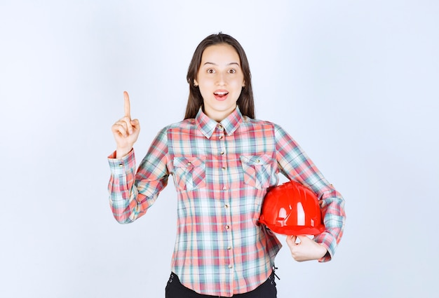 Beautiful young woman holding red helmet and pointing on white background.
