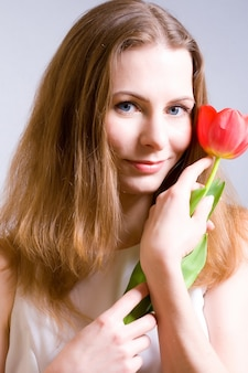 Beautiful young woman holding red tulip