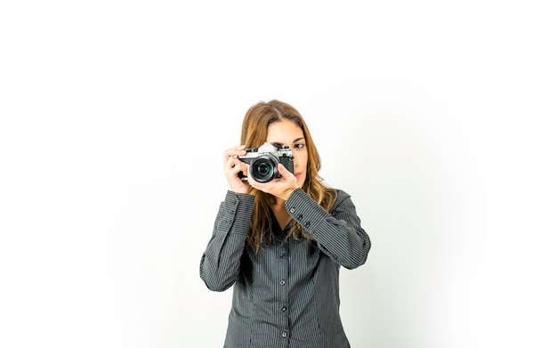 Красивая молодая женщина держа ретро камеру указывая предмет и вращает кольцо фокуса на объективе. винтаж против новых технологий фотографии в наше время. большая копия места для онлайн-фотокурсов adv