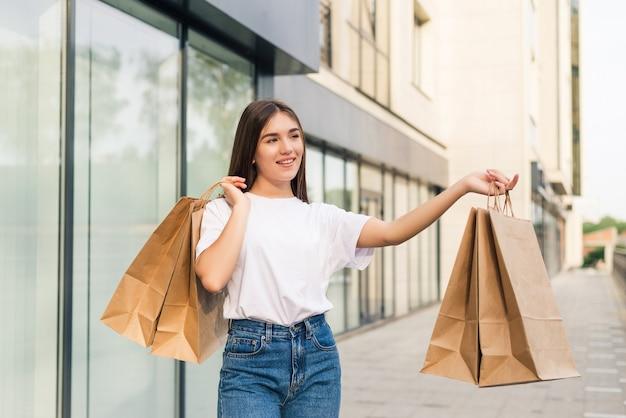 Красивая молодая женщина, держащая хозяйственные сумки и улыбающаяся на открытом воздухе