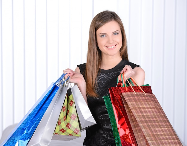 Beautiful young woman holding shopping bags and smiling.