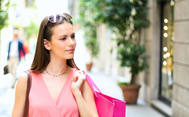 Beautiful young woman holding shopping bags and walking outdoor in a city center