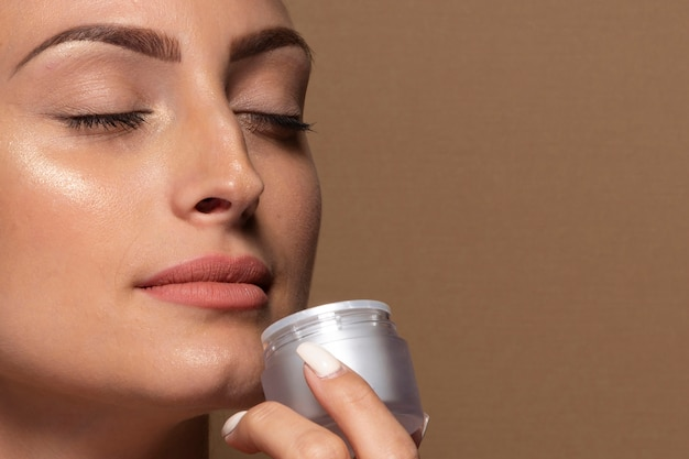 Beautiful young woman holding skin care product
