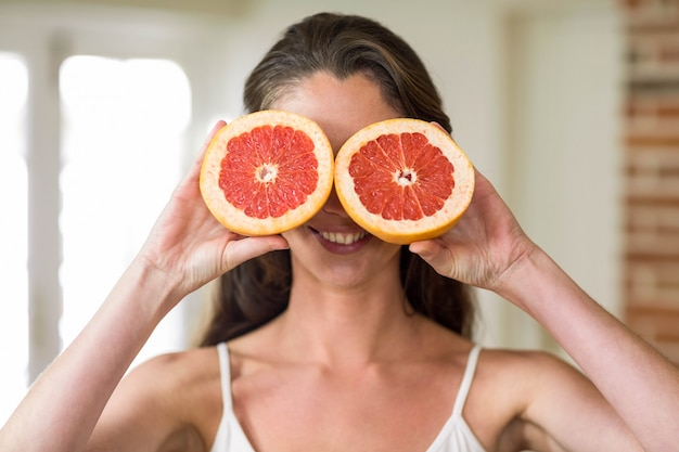 Beautiful young woman holding slices of blood orange in kitchen