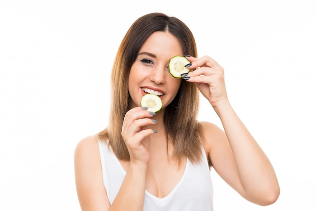 Beautiful young woman holding slices of cucumber