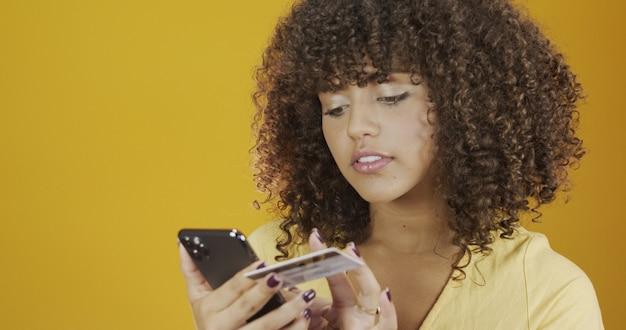 Красивая молодая женщина, держащая смартфон и кредитную банковскую карту. сделка онлайн-покупок. безналичный способ мобильного банкинга. улыбающаяся молодая афро-американская девушка на желтом оранжевом стенном фоне