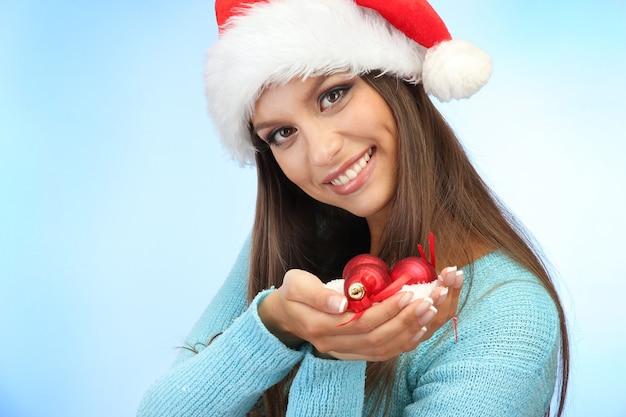 Красивая молодая женщина, держащая снег с елочными шарами, на синем фоне