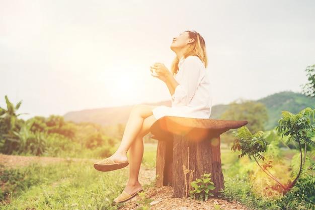 Красивая молодая женщина, подняв чашку кофе, сидя на