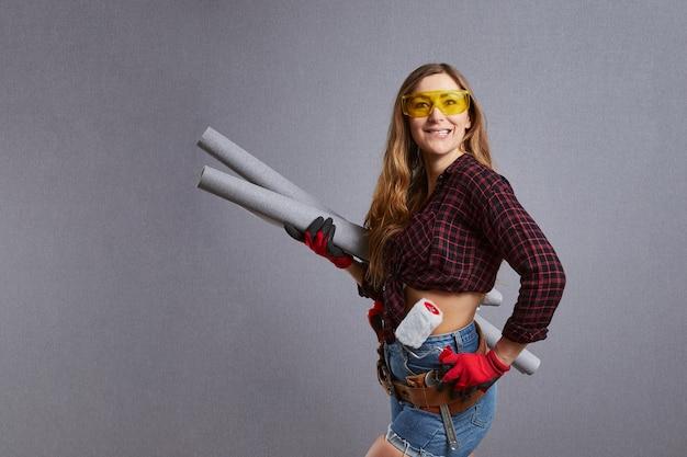 壁紙ロールを保持している美しい若い女性。プロの女性労働者が手にローラーを持っています。幸せな女の子はdiyの修理や塗装の準備をしています。