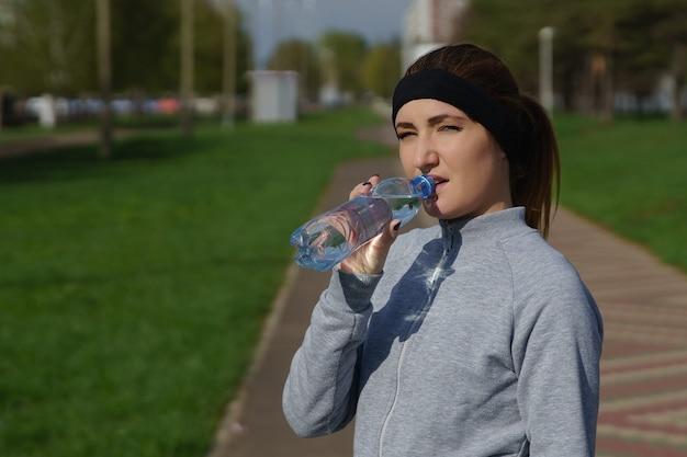 공원에서 훈련 후 물병을 들고 아름 다운 젊은 여자.