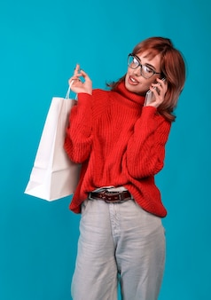 Beautiful young woman holding a white blank paper bag and makes purchases in an online store against