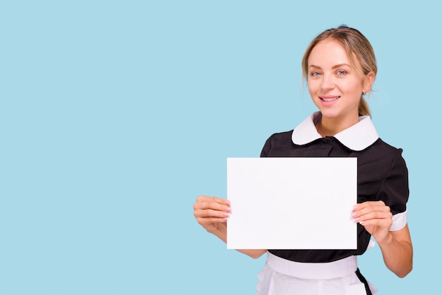 Beautiful young woman holding white blank paper and presenting against blue backdrop