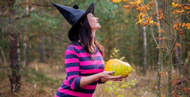 Beautiful young woman holding yellow pumpkin. withch for halloween party