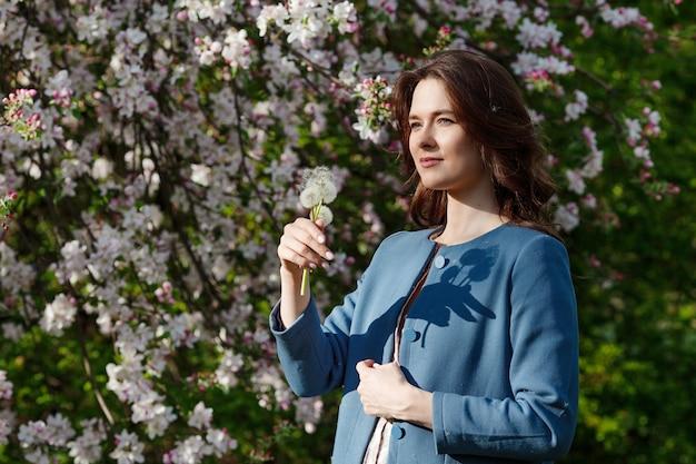 Красивый одуванчик holdinh молодой женщины в весеннем саду. наслаждайтесь природой. здоровая улыбающаяся девочка на открытом воздухе. концепция без аллергии. свобода