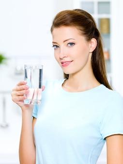 美しい若い女性が台所で水とグラスを保持します。
