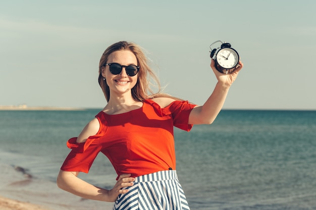 Beautiful young woman holds alarm clock on summer vacation.