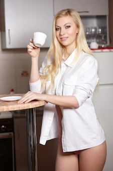 Beautiful young woman holds a cup of coffe on kitchen