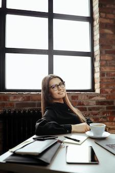 Bella giovane donna in ufficio a casa. lavorare da casa. concetto di telelavoro