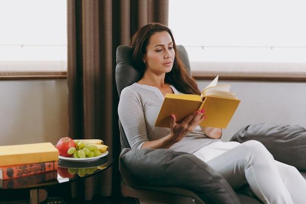 La bella giovane donna a casa seduta su una sedia moderna davanti alla finestra, rilassandosi nel suo soggiorno e leggendo un libro