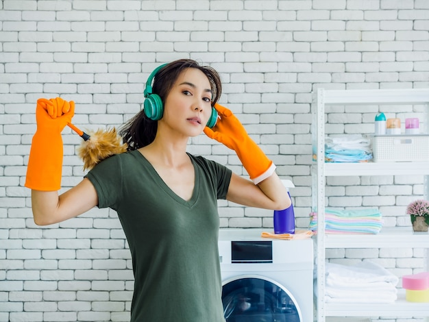 Beautiful young woman, housewife wearing orange rubber gloves, listening music with green headphone and holding feather duster with strong face on white brick wall in home.